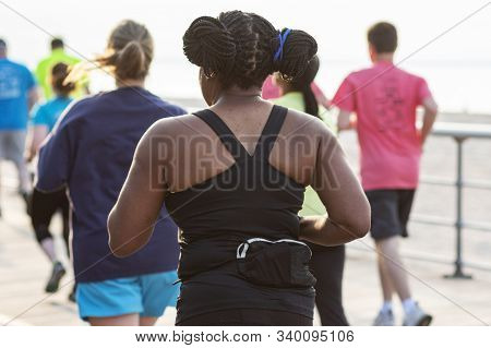 Rear View Of And African American Women And Others Racing A 10k On A Boardwalk Into Sunshine And Car