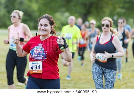 Kings Park, New York, Usa - 17 June 2019: A Runner Racing A 10k Is Smiling And Giving Two Thumbs Up