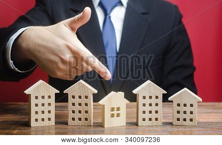 Businessman Chooses A Private House Among Apartment Buildings. Rent Or Buy, Type Of Optimal Convenie