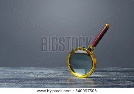 People Look At A Huge Magnifying Glass. Search And Analysis, Analytics And Study. Pay Attention To D