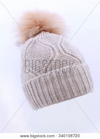 Beige Wool Knit Ski Hat With Faux Fur Pompom Isolated On White. Bobble Hat Topped With Pom Pom Or Lo