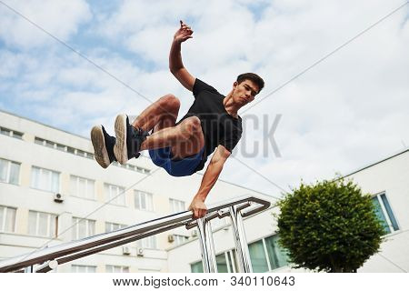 Silver Colored Railings. Young Sports Man Doing Parkour In The City At Sunny Daytime.