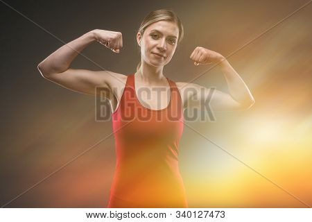Athletic Girl With Muscles On A Dark Background With The Effect Of Radiance.