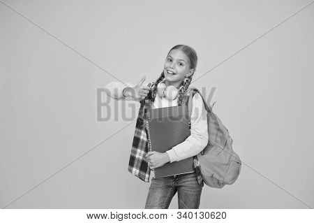 If You Like It Give Thumbs Up. Happy Kid Gesturing Thumbs Up Yellow Background. Little Schoolgirl Sh
