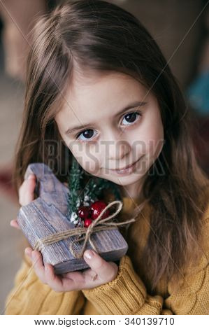 Stock Photo -  Beautiful little girl with wooden christmas rustic decor