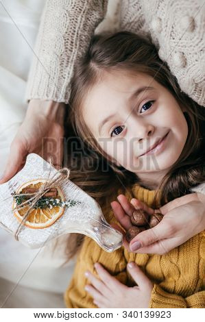 Stock Photo -  Beautiful little girl with nuts on with wooden christmas decor