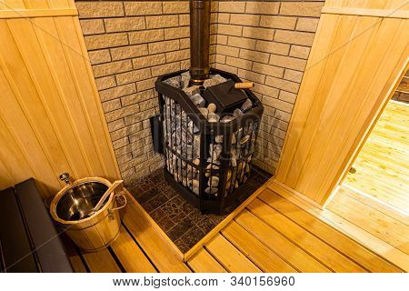 A Close-up Of A Wooden Sauna, A Bath With A Large New Metal Stove And Benches With Beautiful Lamps I