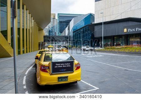Melbourne, Australia - December 14, 2019: Rear View Of Yellow Cab With Public Service Message Agains