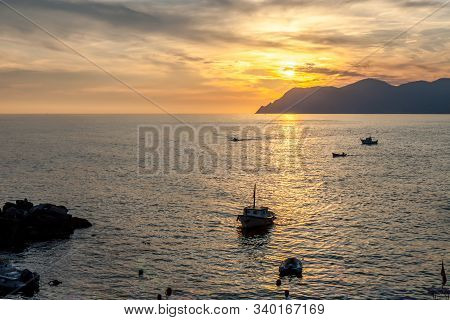 Boat Coming Into Harbor At Sunset On Mediterranean Coast In Cinque Terre Italy