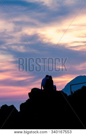 Vertical View Of Couple On Rocks Observing Pink Sunset