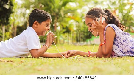 Two Children Having Fun By Playing With String Telephone At Park During Vacation - Concept Of Brain