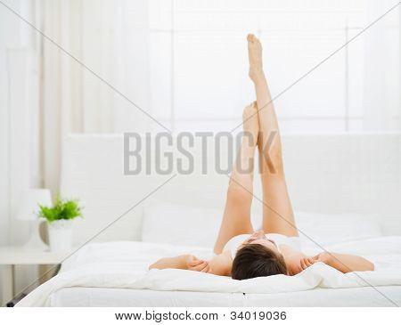 Woman In Bed Enjoying Her Beautiful Legs. Rear View