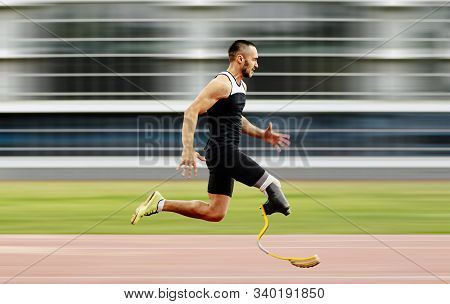 Disabled Athlete Amputee Leg Running With Prosthetic On Background Of Motion Blur