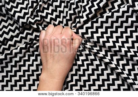 Female Hand Grasping Or Clutching Silk Bed Sheet With Geometric Print In Ecstasy. Sex, Orgasm, Sexua