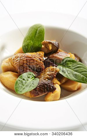 Roasted boletus or porcini mushrooms with baked potatoes and fresh spinach greens on white restaurant plate isolated. Fried delicious ceps, porcino or penny bun healthy dining closeup
