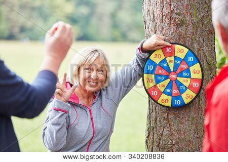 Seniors have fun playing darts together in their free time in nature