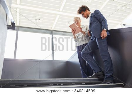 Elderly businesswoman and young trainee do research with tablet computer