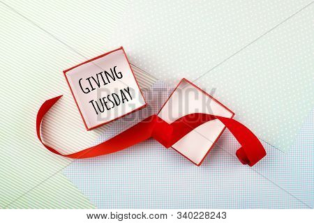 Giving Tuesday Concept. Minimal Flat Lay With Handwriting Text Giving Tuesday In Red Gift Box On Pas