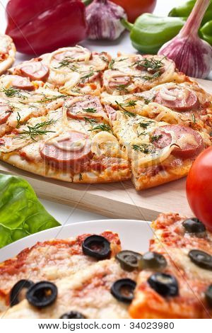 different sliced pizzas with ingredients
