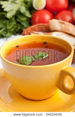 tomato soup in yellow cup with ingredients at the back