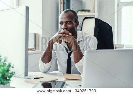 Thoughtful Young African Man In Formalwear Looking Straight While Working In The Office