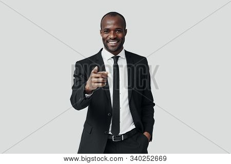 Handsome Young African Man In Formalwear Pointing You And Smiling While Standing Against Grey Backgr