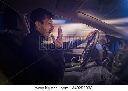 Young Sleepy Man Is Yawning And Driving Car At Night.