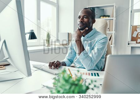 Thoughtful Young African Man In Shirt Using Computer While Working In The Office