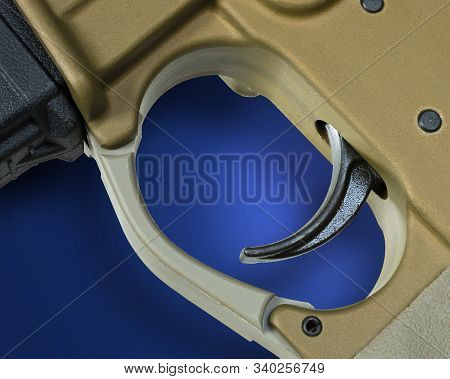 Trigger From An Ar-15 Assault Rifle With Shadown On Blue