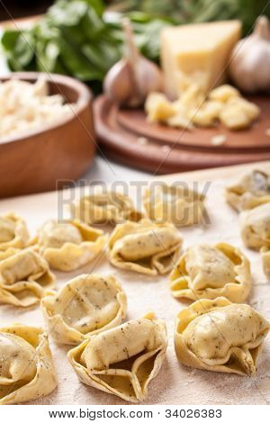 raw stuffed pasta on a cutting board and herbs,cheese and garlic