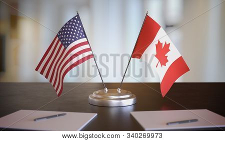 Usa And Canada Flags On Table. Negotiation And Partnership Concept. 3d Rendered Illustration.