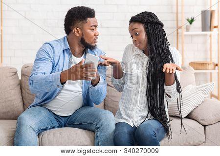Infidelity Concept. Jealous Afro Boyfriend Showing Cheating Girlfriend Her Phone, Demanding Explanat