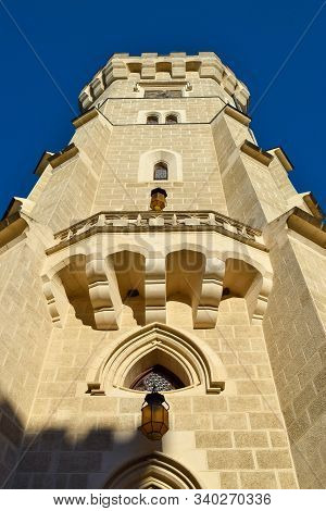 Bottom View Of A Tall Tower In The Sun With Lanterns And Battlements On Roof