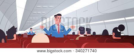 Steward Explaining Instructions For Passengers Male Flight Attendants In Uniform Showing Emergency E