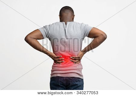 Afro Guy Holding Both Hands Behind His Back, Pain In Spine, Inflamed Zone Highlighted In Red, White