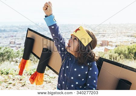Little Child Girl Posing Powerful With Fist In The Air Disguised As A Superhero With Homemade Costum