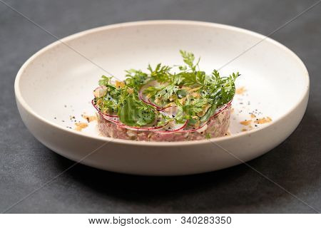Fresh Beef Tartare Dish With Fresh Vegetables In White Plate