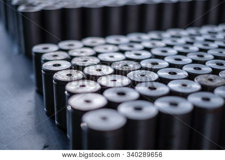 Metal Cylinders Stand On A Table Near The Machine At The Factory. Many Round Metal Parts Lie On The