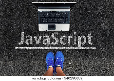 Man Legs In Sneakers Standing Next To Laptop And Javascript On Asphalt