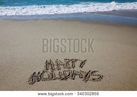 Happy Holidays written in the beach sand. The words Happy Holidays written by the ocean in the sand.