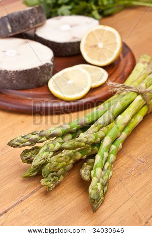 bunch of fresh asparagus and raw fish on a cutting board