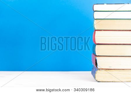 Stack Of Old Books, Blue Background, Free Copy Space. Antique Old Hardback Books On A Wooden Shelf O