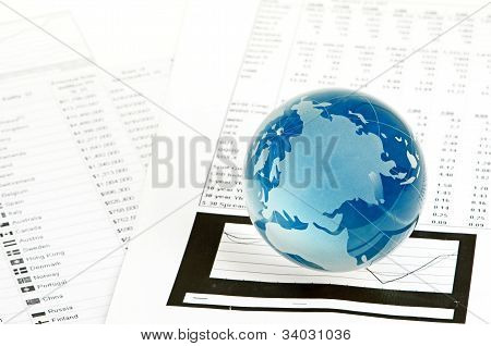 Glass globe and pen on finance chart