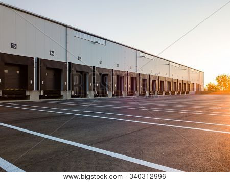 Warehouse exterior with loading ramps and slots for trucks to park - modern industry warehouse storage building.