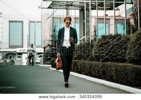 The Well-dressed Businessmen Is Walking Down The Green City Street And Reading Something In His Mobi