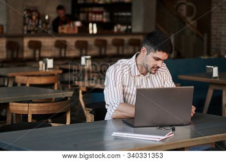 Waiting For The Results. Adult Man Sits In Cafe At Daytime And Using The Laptop For The Remote Work.