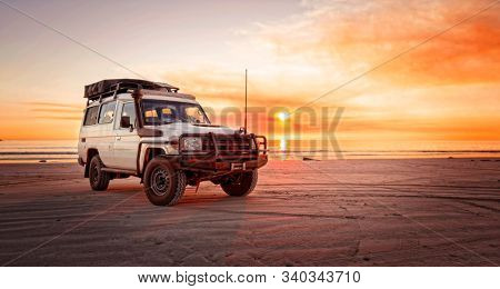 Western Australia – Outback adventure with  car at the beach of an ocean at sunrise and a bloodred sky
