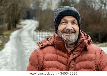 Happy smiling elderly bearded man face, winter portrait outdoors in a Russian village near the road