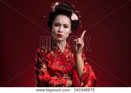 Image of strict asian geisha woman in traditional japanese kimono gesturing finger in punishment isolated over red background