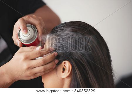 hairdresser fixing a coiffure with ringlets of a woman using a hair spray in a beauty salon. concept of professional stylist training poster